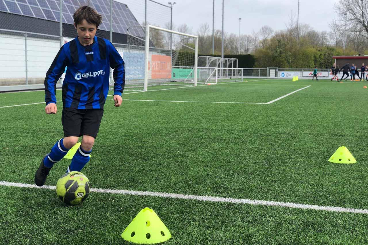 Speler legt dribbelparcour af tijdens een voetbalkamp - Soccertime