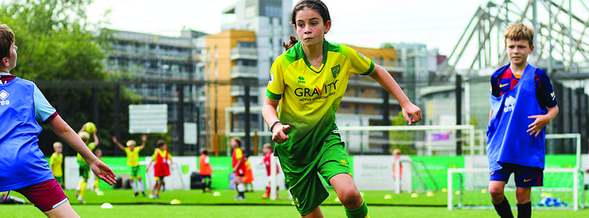 Jongetjes en meisje voetballen in een Errea voetbaltenue tijdens de zomerstage - Soccertime
